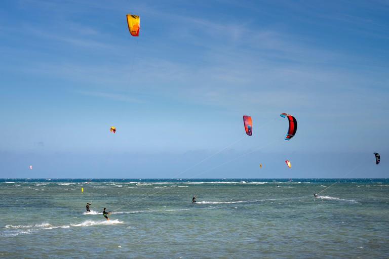 2B1HFWW Ninh Chu beach, Ninh Thuan province, Vietnam - 9th January 2020: Tourists Kitesurfing on the waves of the sea the beach on a sunny day at Ninh Chu bea