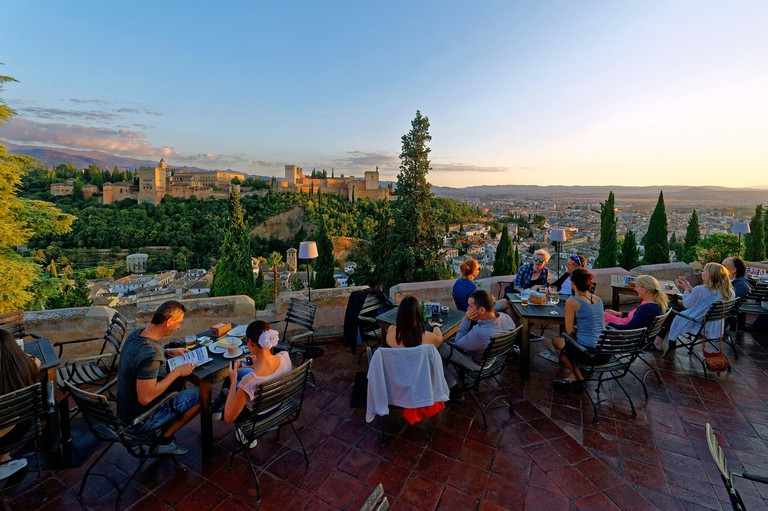 Spain, Andalusia, Granada, the Alhambra Palace, listed as World Heritage by UNESCO, built between 13th and 14th century by the Nasrides dynasty, islamic architecture, the Sierra Nevada in the background, the terrace of restaurant El Huerto de Juan Ranas