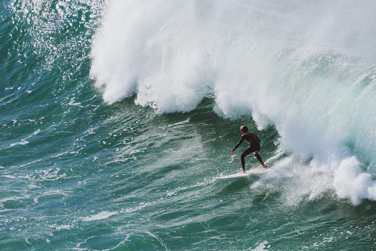 Surfer on Blue Ocean Wave . Surf spot in Ericeira Portugal