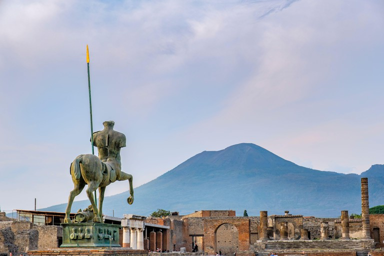 2BEM7D7 Pompeii ruins, Pompeii Forum - Centauro, bronze statue by Igor Motoraj, Mount Vesuvius on background, ancient city of Pompeii, Italy, Europe.