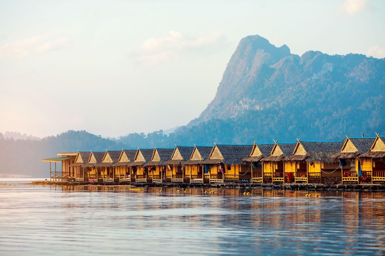 Floating Bungalows at Khao Sok National Park with Cheow Lan lake and mountains at sunrise, Thailand.