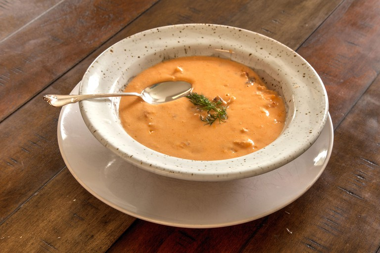 Fresh Seafood meal of Lobster bisque soup in a bowl on a white plate.
