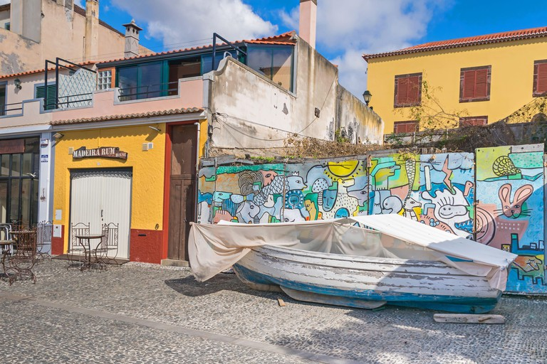 """Funchal, Portugal -  November 10, 2019: Fishing boat and painted wall on the street Rua Portao de Sao Tiago as part of the  """"ArT of opEN doors project"""