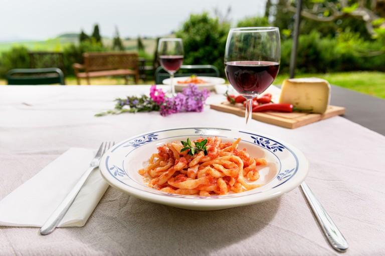 2BM6DJA Italian dish, handmade spaghetti pasta, pici with tomato sauce on a table in the garden outdoors.