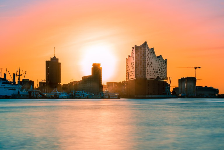 colorful skyline from the port of Hamburg at sunrise with Elbphilharmonie photographed from the opposite side of the Elbe. near the old elbe tunnel.