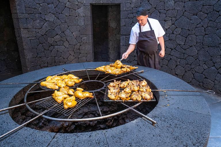 Spain, Canary islands, Lanzarote island, Timanfaya National Park or Montanas del Fuego, the restaurant El Diablo uses a grill located above a volcanic chimney