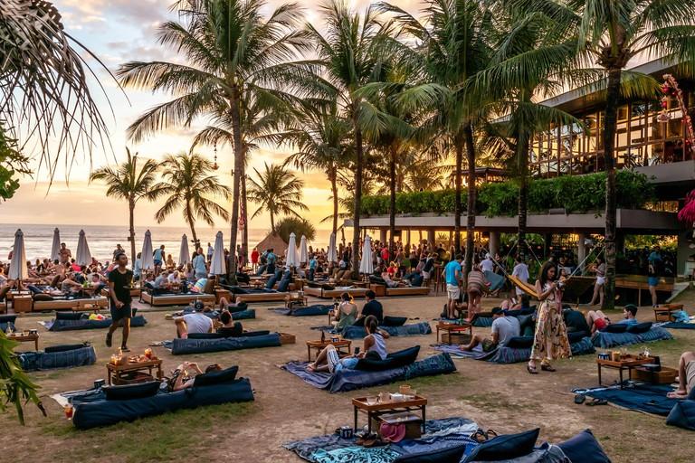 2C567YR Seminyak, Bali / Indonesia - September 09 2018: Australian tourists enjoy drinks and watch a warm sunset at the world famous Potato Head Beach Club