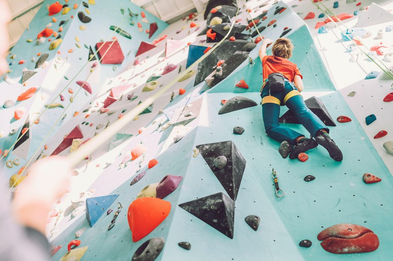 Teenager boy at indoor climbing wall hall. Boy is climbing using a top rope and climbing harness and somebody belaying him from floor. Active teenager