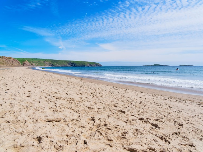 The wide expanse of Aberdaron beach in Wales on a bright spring day.