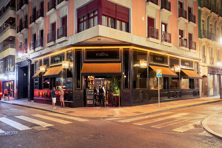 Nightime Exterior view of El Portal restaurant and cocktail bar in Alicante City, Spain, Europe, a couple smokes and the staff wave