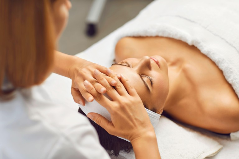 Facial skin beauty and health concept. A woman receives a facial massage from a clinic beautician