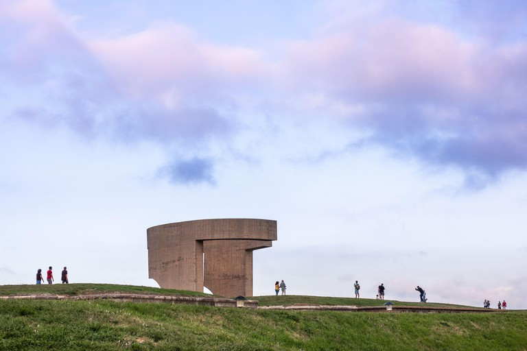 """Spain; Sep 2020: """"Elogio del Horizonte"""" (Eulogy of the Horizon), by Eduardo Chillida. Famous monument by the sea made of concrete. People walking by,"""