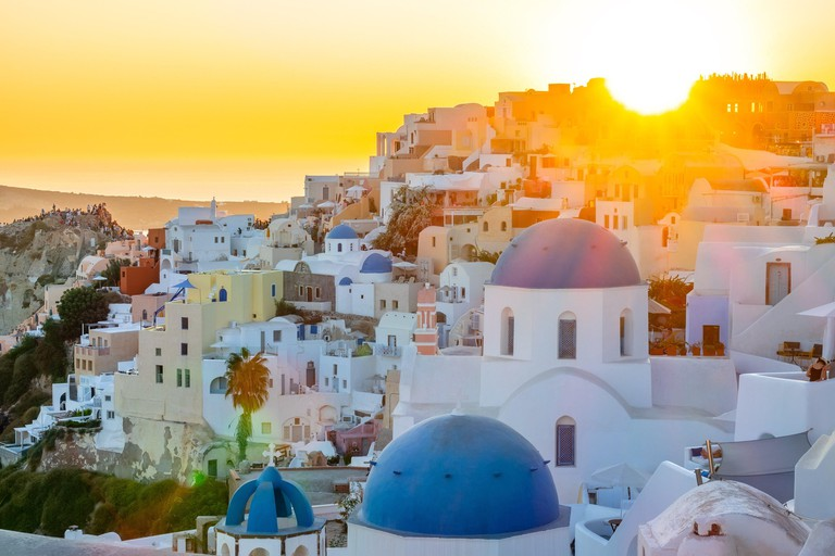 Greece. Oia town on Santorini island. Sunset over the roofs of buildings on the caldera.