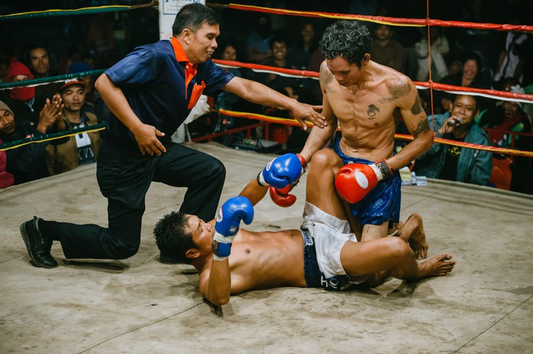 Muay Thai fight in isan, rural Thailand, Thai boxing, the referee trying to stop boxer from punching opponent lying on the ground.