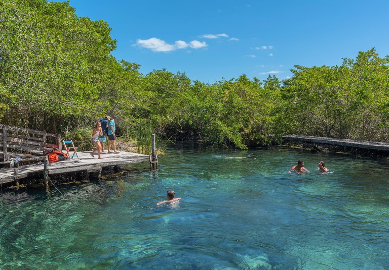 2F6DFHE Tourists swim at the Hoyo negro Yalahau water hole, Isla Holbox, Mexico