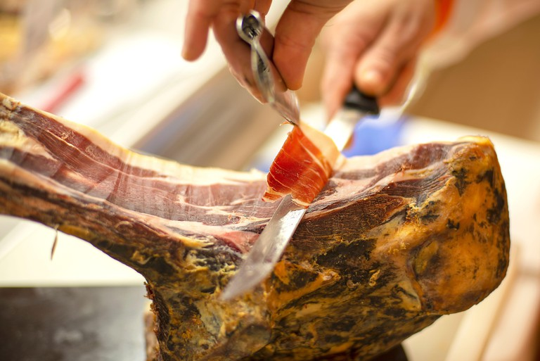 2F9J9Y8 Close-up on person's hands slicing delicious cured cured ham carving