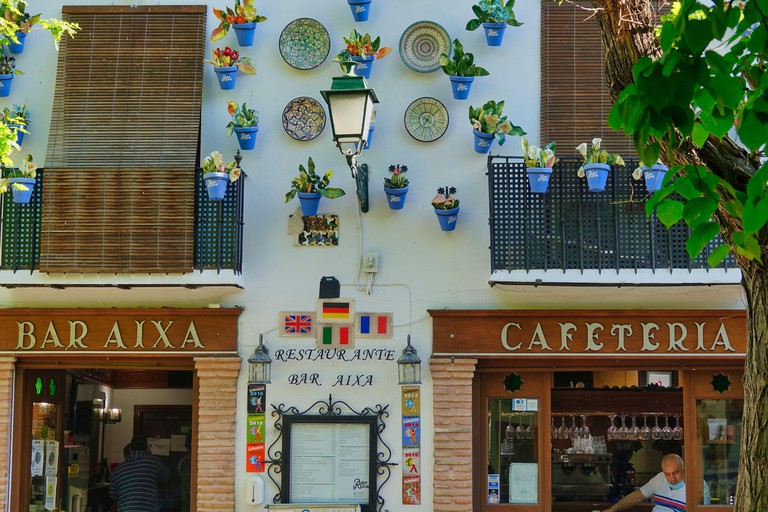 Facade with colorful ceramic decorations of a traditional cafeteria in the Albaicin neighborhood of Granada (Spain) with the waiter at the entrance