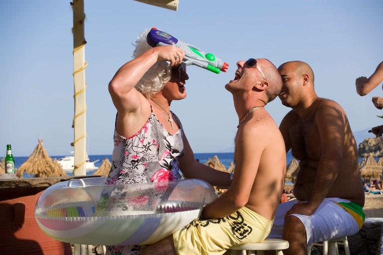 Man wearing crazy woman clothes Super Paradise Beach Mykonos Greece