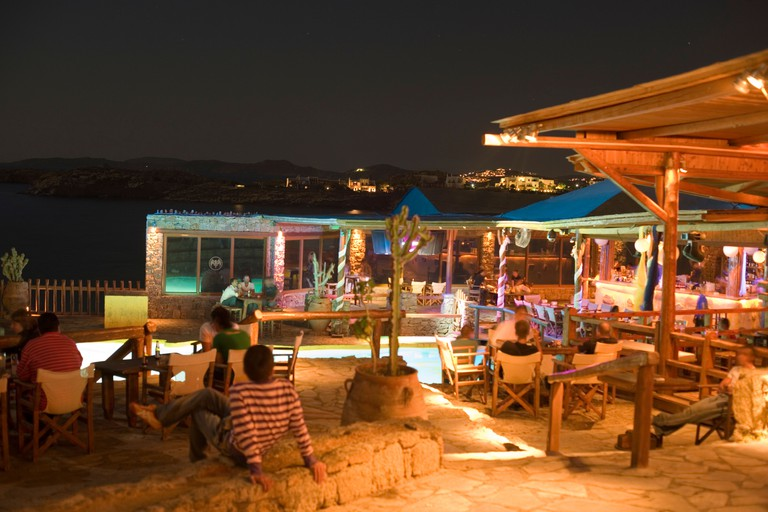 AC28RE Tourists sitting in the open air club of Cavo Paradiso Paradise Beach Mykonos Greece