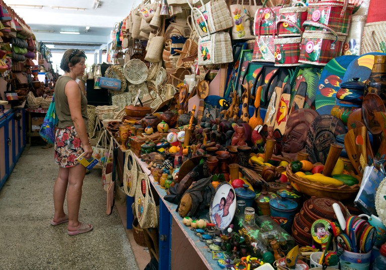 """A tourist shopping for local crafts in the market, Castries, St Lucia, """"West Indies"""" Caribbean. Image shot 08/2008. Exact date unknown."""