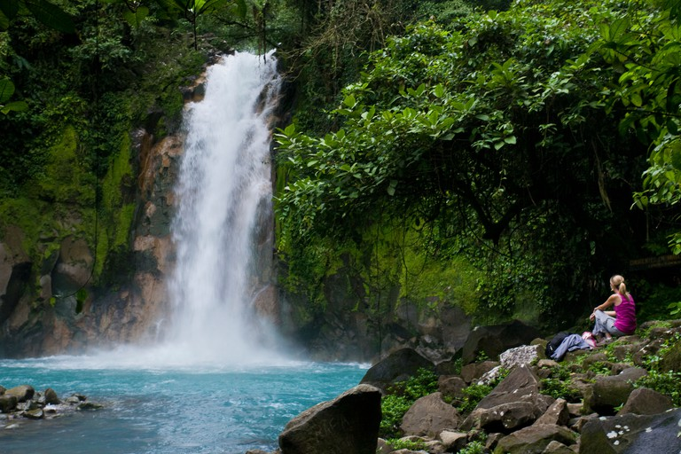 BDE275 Female hiker resting beneath a waterfall along the vibrant blue Rio Celeste river in Tenorio Volcano National Park, Costa Rica