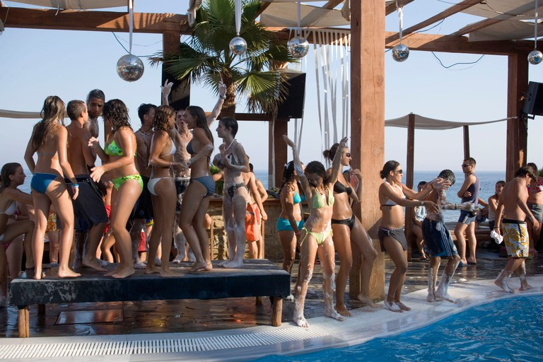 BKYBFM Young people dancing during a beach party at a pool of the Paradise Club, Paradise Beach, Mykonos, Greece