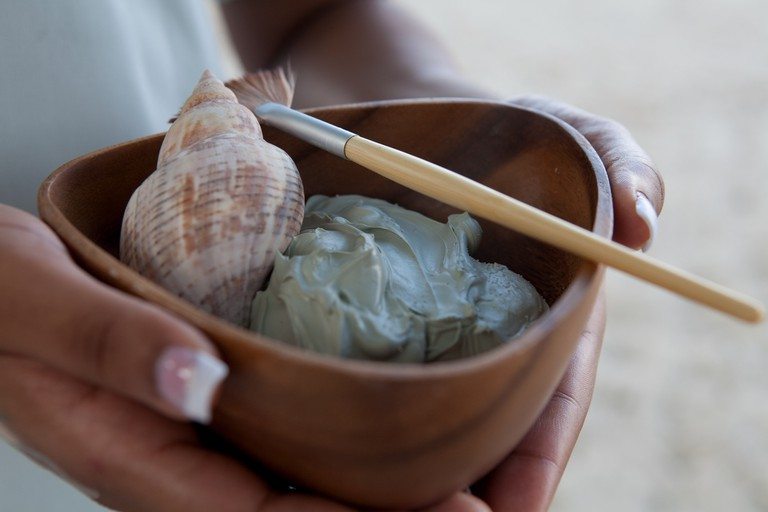 Person holding bowl of mud face mask and shell at spa