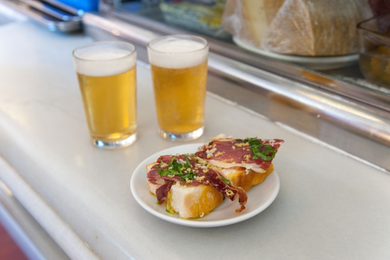 Close up of tapas of Jamon Serrano and beers on bar counter, Madrid, Spain