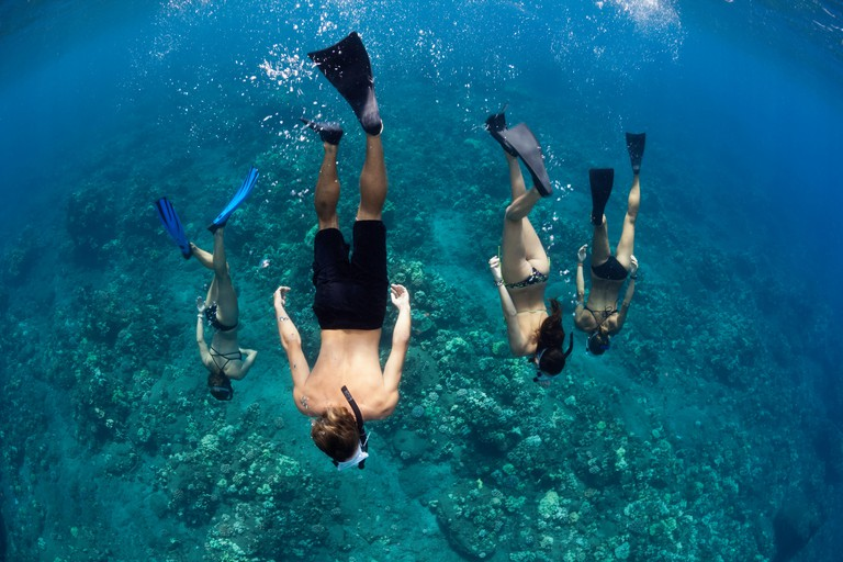 A group of young people (MR) free diving off the island of Lanai, Hawaii.