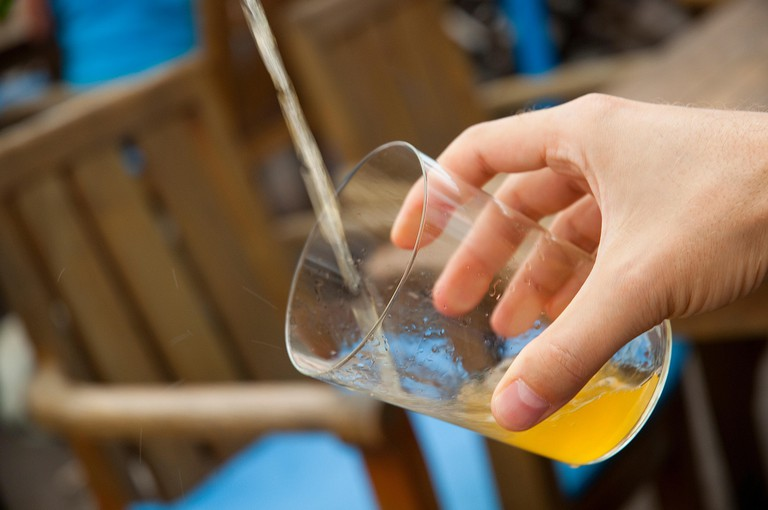Man´s hand serving cider. Asturias, Spain.