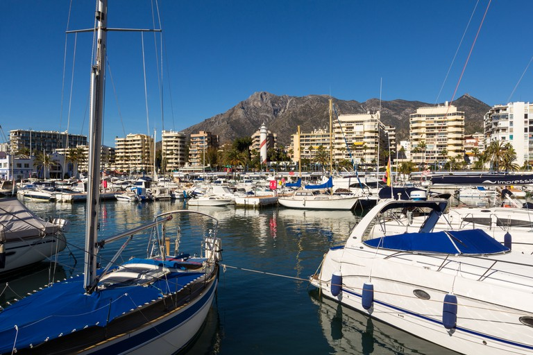 MARBELLA SPAIN SEA FRONT WITH LIGHTHOUSE AND BOATS IN THE HARBOUR