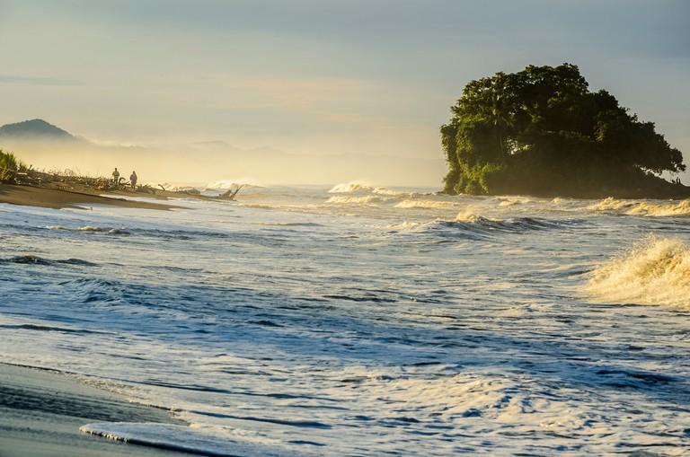 Tourist watching the sunrise on the Bahia Solano beach