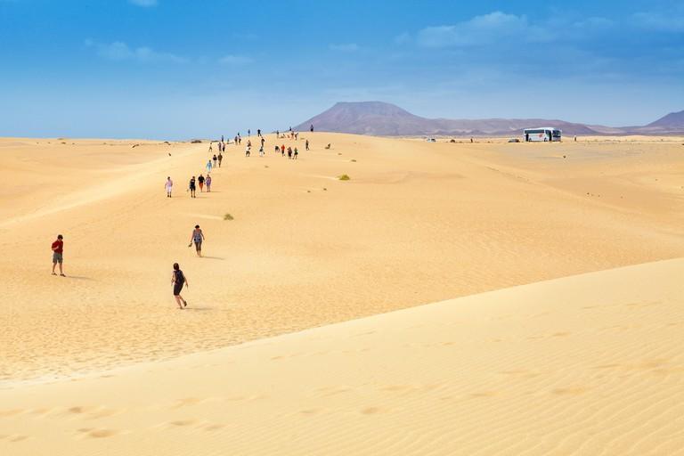 Fuerteventura Island, tourists walking on sand dunes in Parque Natural de Corralejo, Spain, Canary Islands