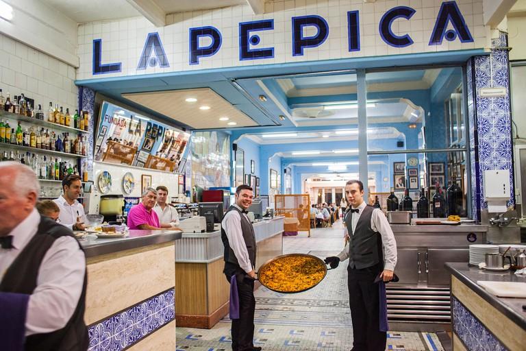 FDAM1J Waiters show a paella. In La Pepica restaurant,6 Passeig Neptu,Malvarrosa beach.Valencia, Spain