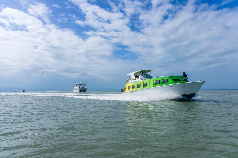 Shuttle boats transport tourists from a cruise ship to the port dock.  Belize City, Belize