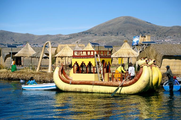 Yellow totora reed boat and houses on totora reed island, Uros Islands, Lake Titicaca, Puno, Peru