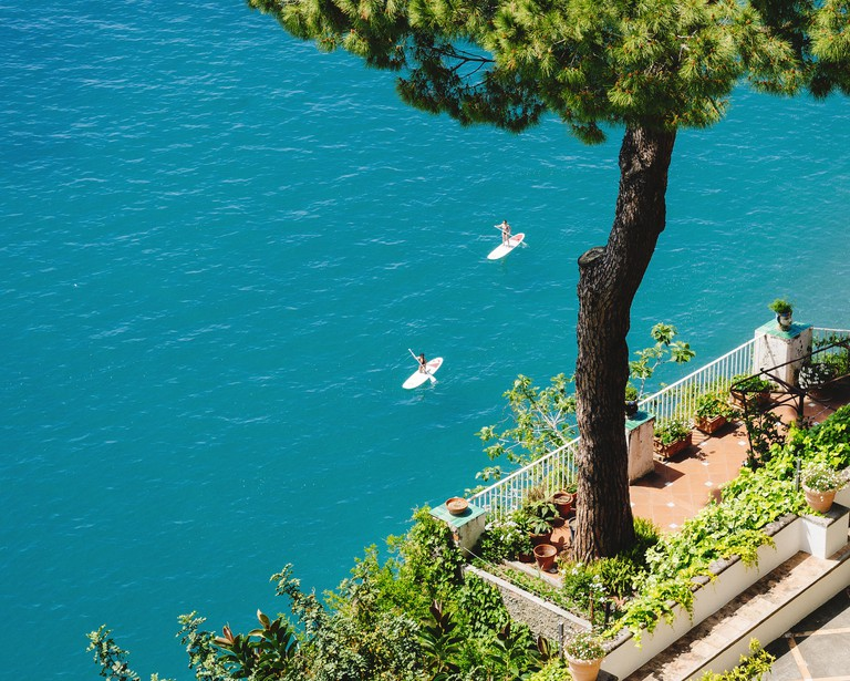 High-angle view to a balcony with a pine tree and two women stand up paddling in the clear blue sea