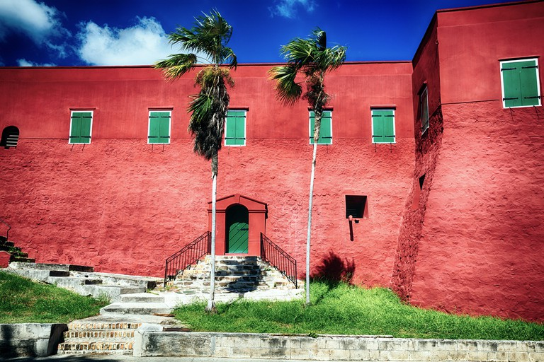 GH4C8E Low Angle View the Red Walls and Green Shutters of Fort Christian, Charlotte Amalie, St Thomas, US Virgin Islands