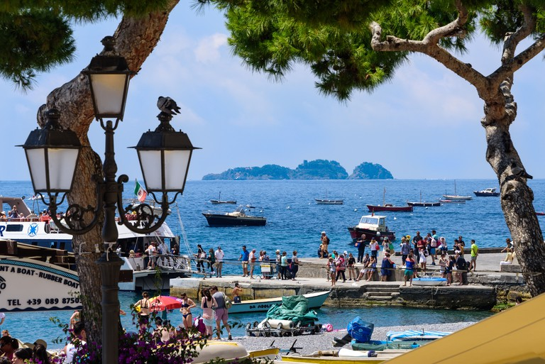 Tourists gather at a boat marina for boat tours along the Amalfi Coastline in Italy.