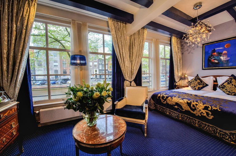 A bed, drapes and table and chair in an opulent hotel room at Ambassade Hotel