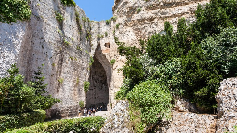 travel to Italy - tourists near Orecchio di Dionisio (Ear of Dionysius) cave in Temenites Hill in latomie del paradiso area of Archaeological Park of