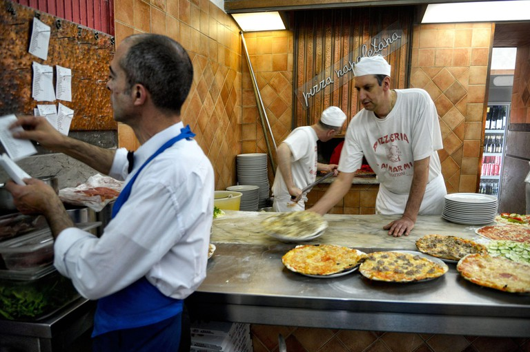 Italy, Lazio, Rome, historical centre listed as World Heritage by UNESCO, district of Trastevere, pizzeria Ai Marmi, pizza cook taking out pizza of an