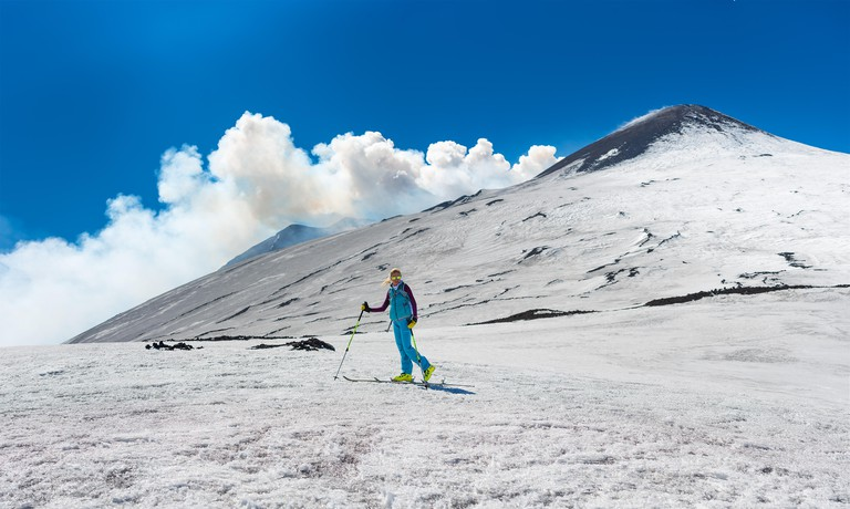 Girl ski touring under the top of the crater of Mount Etna Sicily Italy