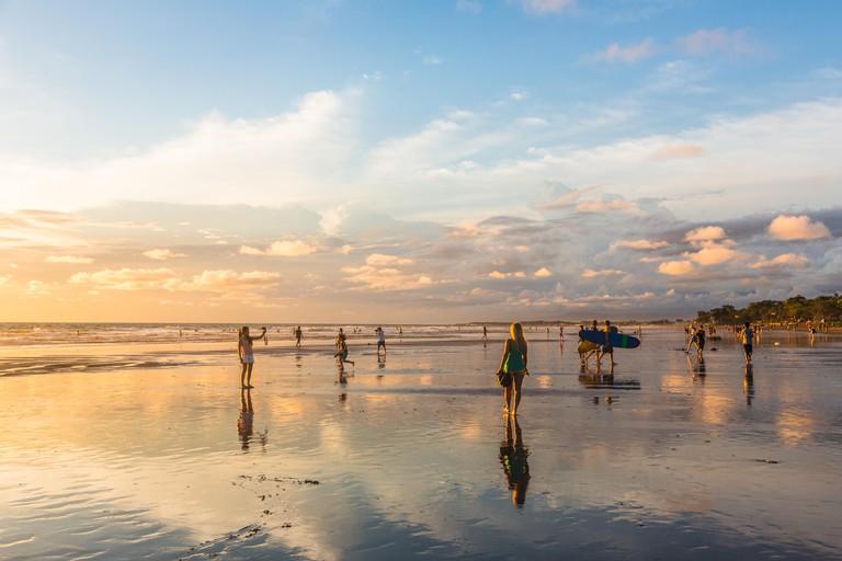 BALI, INDONESIA - FEBRUARY 21, 2016: Tourists enjoy a stunning sunset on Kuta beach in the Seminyak area of the popular island in Indonesia.