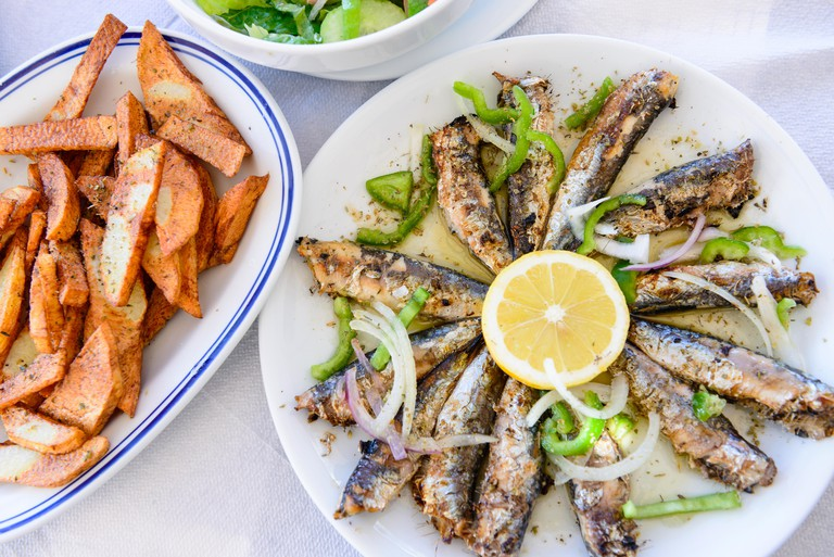 J91JP2 Freshly grilled sardines on a plate with lemon and fried potatoes