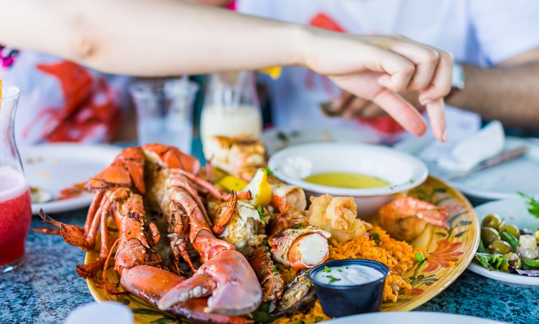 Closeup of lobsters and seafood on plate with hand reaching for garlic butter