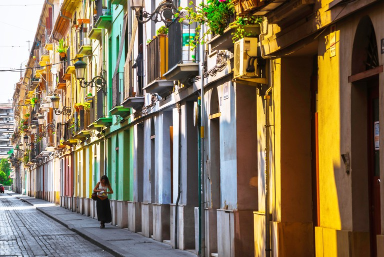 K9GNK0 Valencia Spain city, view of a young woman walking alone through a colourful street in the old town Barrio del Carmen quarter of Valencia, Spain