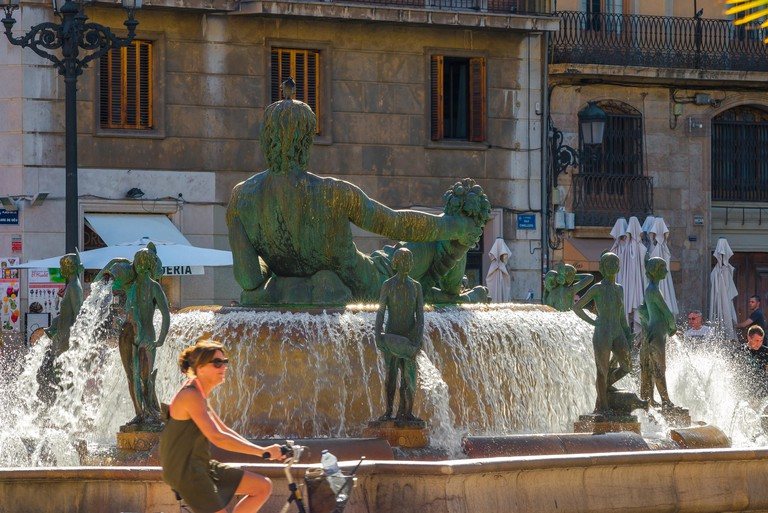 KD5FX1 Spain city summer, view of a woman riding her bike past the Turia Fountain in the Plaza de la Virgen in the center of Valencia on a summer day, Spain