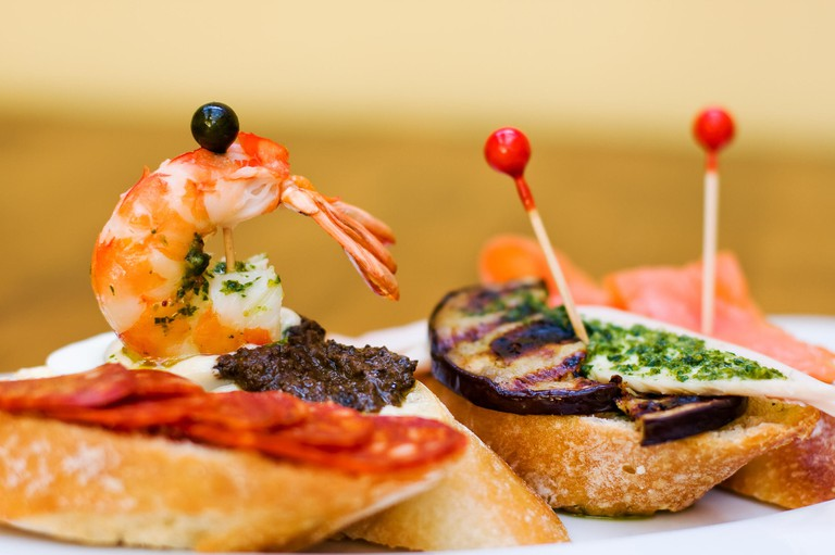 Traditional Spanish Cuisine snacks. Tapas baguette canape with chorizo sausages, black olives, grilled eggplant, salmon and marinated shrimp