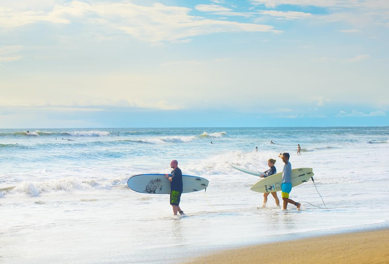 KJHF91 CANGGU, BALI ISLAND, INDONESIA - JAN 19, 2017: Group of surfers going to surf in the beach. Bali island is one of the worlds best surfing destinations